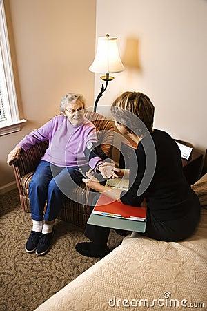 Mulher idosa que tem a pressão sanguínea tomada