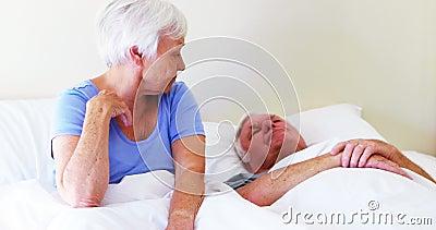 Mulher irritada que cobre suas orelhas quando homem que ressona na cama vídeos de arquivo