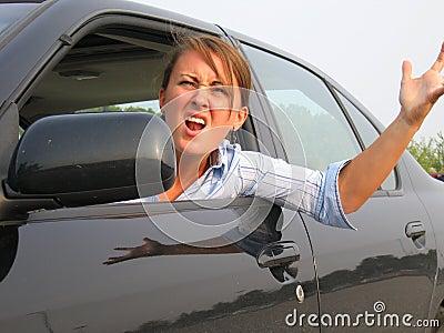 Mulher irritada que grita para fora o indicador de carro