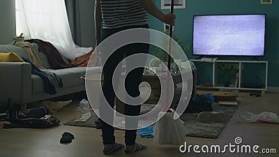 A mulher joga a cubeta e o espanador devido à confusão na sala de visitas após o partido vídeos de arquivo