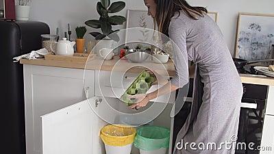 Mulher joga garrafas de vidro e plástico em recipientes de diferentes cores para coleta separada de lixo alimentar em cozinha mod vídeos de arquivo