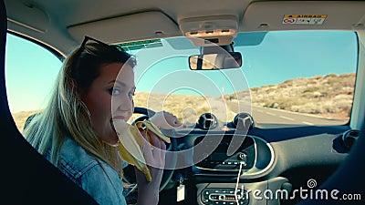 Mulher loira atrativa comendo uma banana como símbolo de homens, sentada no assento do motorista de um carro e segurando o vídeos de arquivo