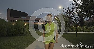 Mulher loura em treinamento running do desgaste da aptidão na passagem do parque Dianteiro depois da vista Noite ou noite do verã video estoque