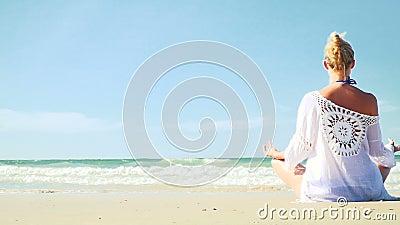 Mulher loura nova que faz a ioga na praia video estoque