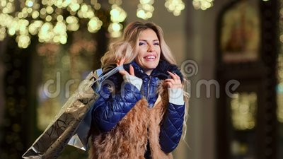 Mulher luxuosa de sorriso do retrato com os sacos de compras cercados por luzes amarelas do brilho do Natal vídeos de arquivo