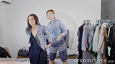 A mulher moreno nova está aplicando o revestimento das calças de brim e está consultando-o com seu imagem-fabricante pessoal na c filme