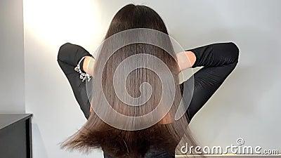 Mulher moreno que acena seu cabelo bonito, saud?vel ap?s um tratamento em um sal?o de beleza vídeos de arquivo