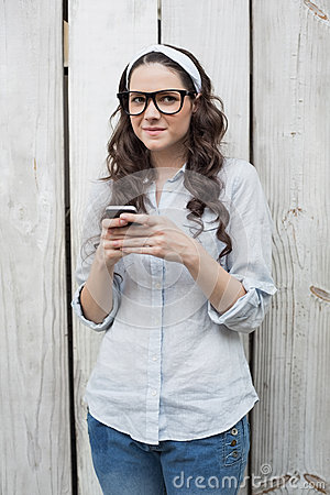 Mulher na moda pensativa com os vidros à moda que enviam a mensagem de texto