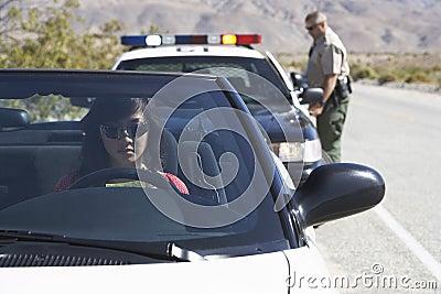 Mulher no carro que está sendo puxado sobre pelo agente da polícia