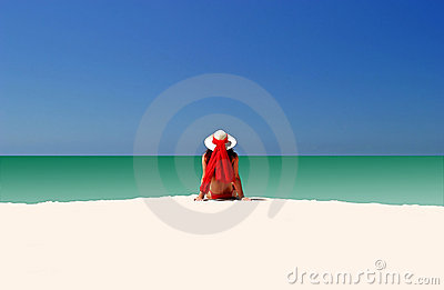 Mulher no chapéu vermelho e no biquini que sentam-se toda sozinho na praia vazia