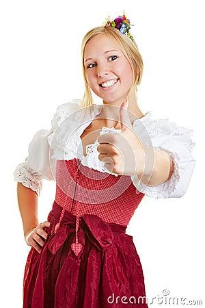 Mulher no dirndl que mantem os polegares