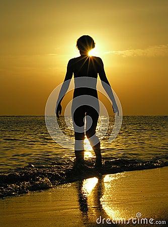 Mulher no nascer do sol com o sol na cabeça