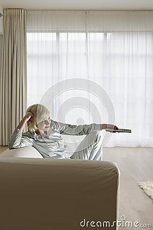 Mulher no sofá que olha a tevê