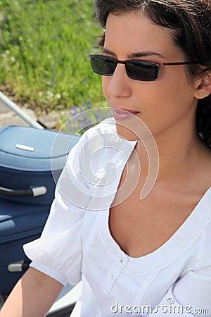 Mulher nos óculos de sol que sentam-se ao lado de suas malas de viagem