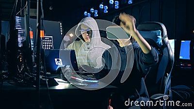 A mulher nos VR-vidros e seu colega masculino estão cortando vídeos de arquivo