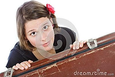 Mulher nova atrás da mala de viagem