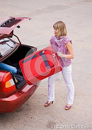 Mulher nova com uma mala de viagem vermelha no carro
