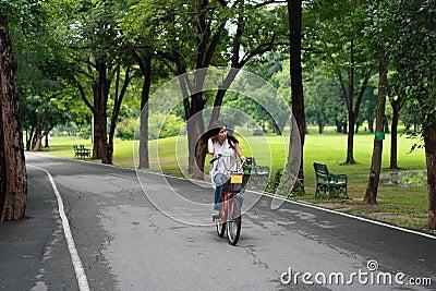 Mulher nova feliz que relaxa sobre a bicicleta
