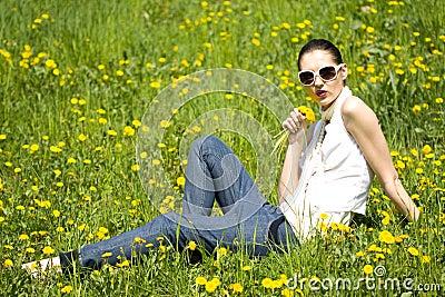 Jovem mulher na natureza que cheira uma flor