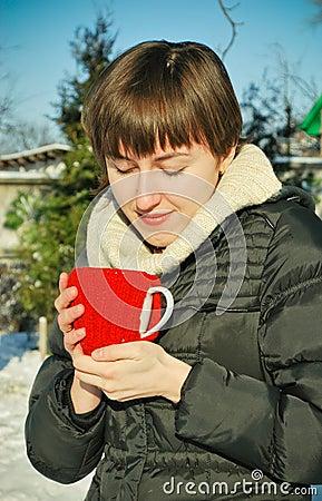 Mulher nova que bebe o chá quente ao ar livre