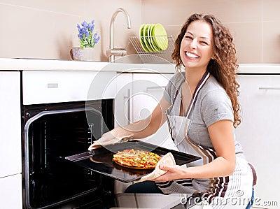 Mulher nova que cozinha a pizza
