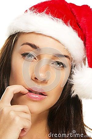 A mulher nova que desgasta o chapéu de Santa põr sua ponta do dedo t