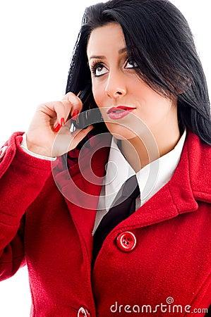 Jovem mulher que fala no telefone e que olha para cima