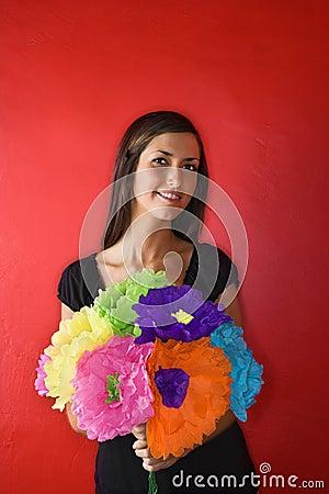 Mulher nova que prende as flores de papel. Isolado