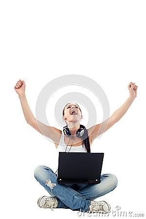 Mulher nova que senta-se com o portátil que levanta as mãos