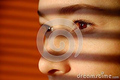 A mulher olha através do jalousie