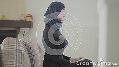 Mulher oriental de sorriso nova na roupa traseira e na mantilha bonita que sentam-se com parte traseira reta no sofá em casa vídeos de arquivo
