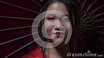 A mulher oriental elegante desdobra um fã vermelho com um sorriso, e cobre sua cara com ela, movimento lento vídeos de arquivo
