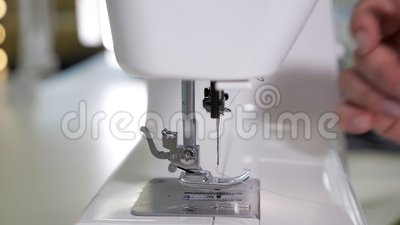 A mulher põe a linha na agulha na máquina de costura que prepara-se para trabalhar, close up das mãos filme