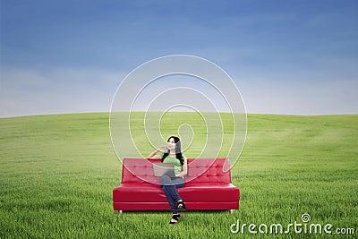 Mulher pensativa no sofá vermelho no campo verde