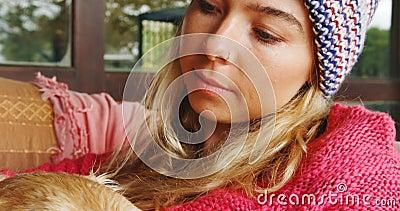 Mulher pensativa que afaga seu cão no sofá em casa 4k video estoque