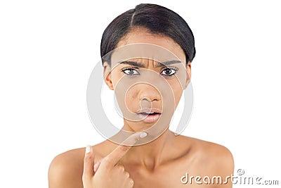 Mulher preocupada que aponta no enrugamento em seu queixo