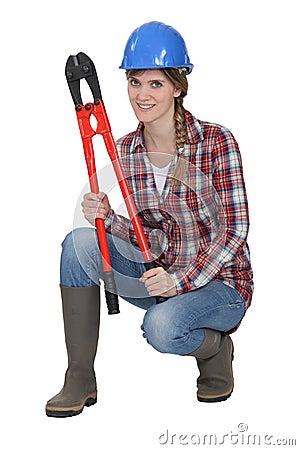 Mulher que agacha-se com cortadores de parafuso