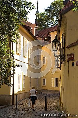 Mulher que anda através da rua em Europa velha