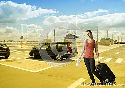 Mulher que anda com sua mala de viagem no lugar de estacionamento do carro