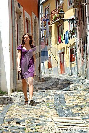 Mulher que anda em uma rua estreita de Portugal