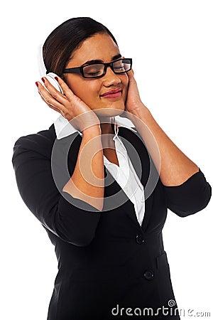 Mulher que aprecia a música através dos fones de ouvido