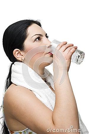 Mulher que bebe um vidro da água