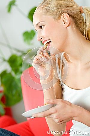 Mulher que come e que presta atenção à tevê
