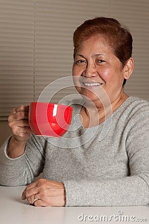 Mulher que come o café