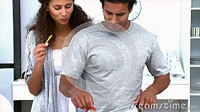 Mulher que come quando seu marido cozinhar vegetais video estoque