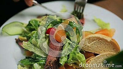 Mulher que come a salada no restaurante, tiro do steadycam video estoque