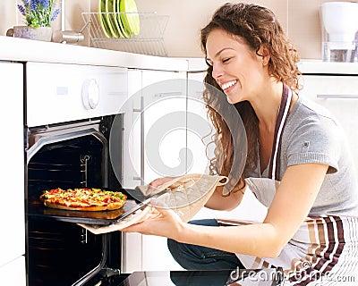 Mulher que cozinha a pizza