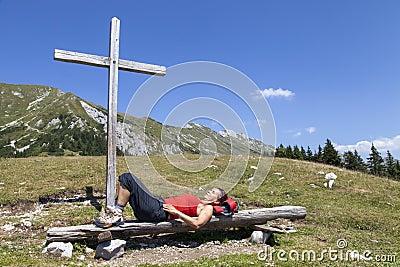 Mulher que descansa sob a cruz de madeira