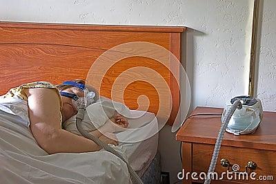 Mulher que dorme com uma máquina de CPAP