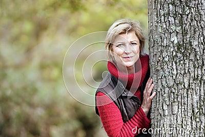 Mulher que esconde atrás de uma árvore